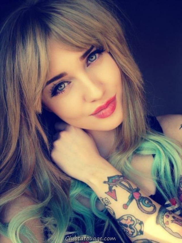 femme aux yeux bleus et doux visage, couvrant son cou Sorie, on voit un tatouage sur son avant-bras noueux ancre