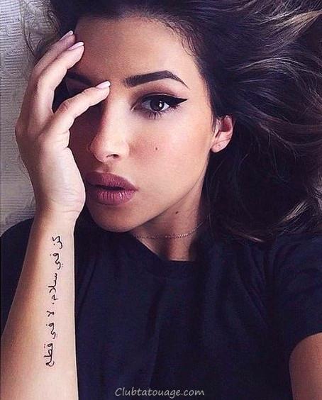 fille brune nous regarde du lit, portant tatouage sur les araves avant-bras lettres