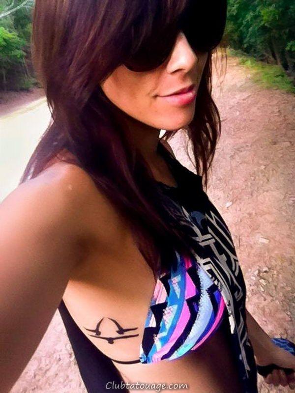brune dans la femme de la forêt, le port de lunettes de soleil et des sourires, a dans son tatouage nervures trois colombes formant signe dièse