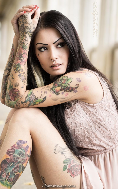 spectaculaire femme latina assis, nous voyons ses tatouages dans des couleurs de style nouvelle école