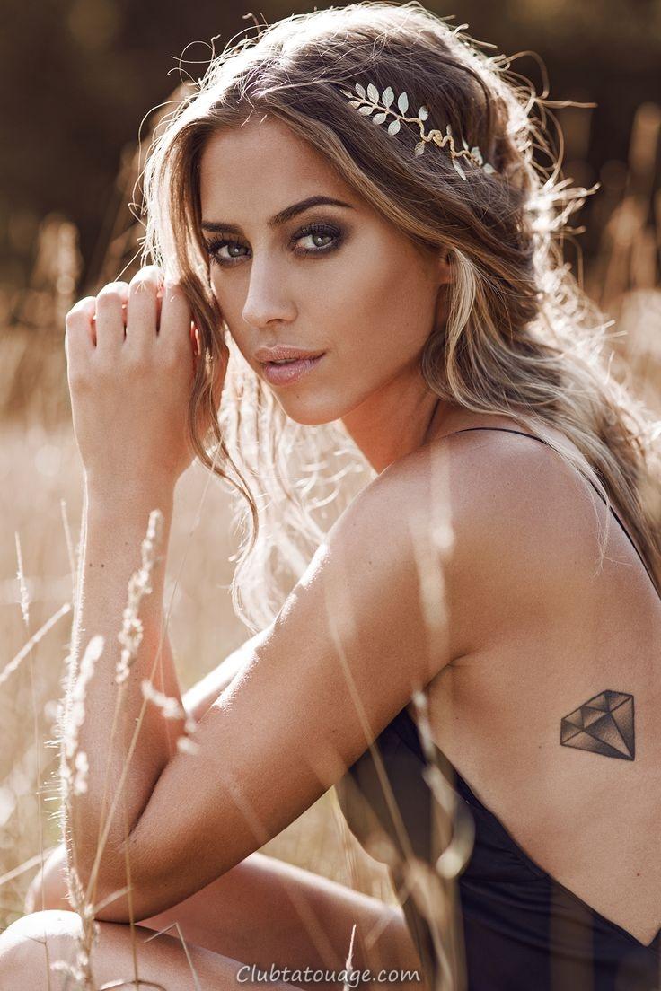 hippie fille avec quatre triangles tatouage sur le bras