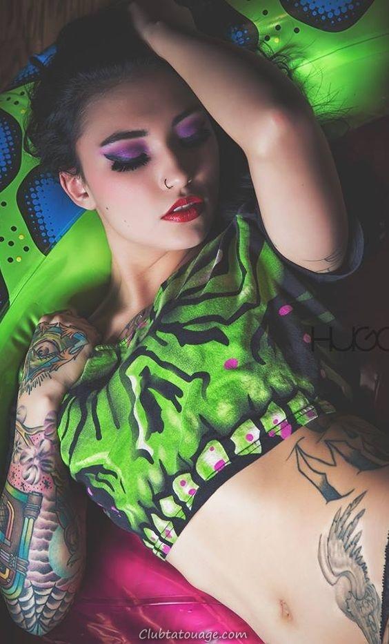 Nous voyons une femme allongée sur un matelas gonflable vert, la fille porte des tatouages sur l'avant-bras d'un juke-box, et le tatouage d'ailes sur le hip