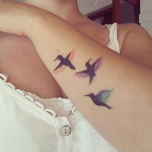 trois colibris avec des plumes orange et bleu violet